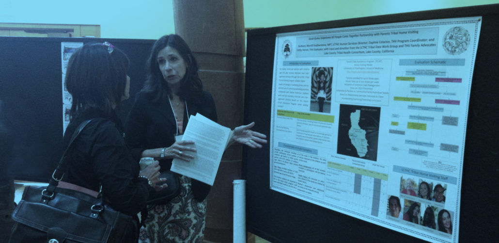 Two women talking in front of a conference poster.